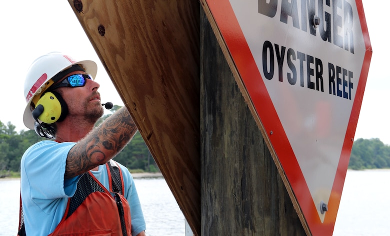 """man in life jacket holds up sign that reads, """"DANGER Oyster Reef"""" while placing it on a pole in the water."""