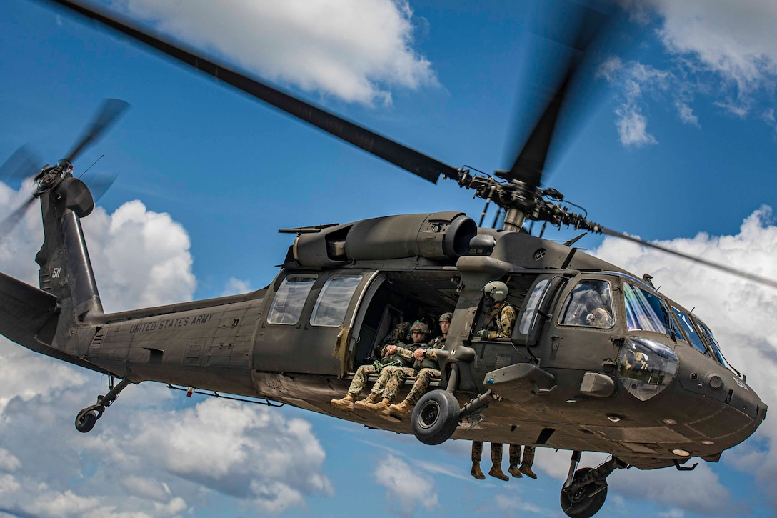 Marines sit in a helicopter's door as it flies through the sky.