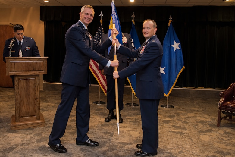 Maj. Gen. Craig Wills, 19th Air Force commander, passes the guidon to Col. Craig D. Prather, 47th Flying Training Wing commander, during the virtual wing change of command ceremony at Laughlin Air Force Base, Texas, July 31, 2020. Prather takes command after serving as the commander of the 1st Joint Special Operations Air Component at Fort Bragg, N.C. (U.S. Air Force photo by Senior Airman Marco A. Gomez)