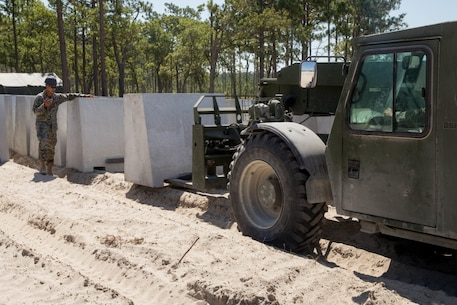U.S. Marine Corps Lance Cpl. Martin Lebron, a heavy equipment operator with 2d Engineer Support Battalion, guides a forklift operator to place a barricade on Camp Lejeune, North Carolina, July 27, 2020. Range G-6 was modified by 2d Combat Engineer Battalion to allow for advanced company level offensive and defensive operations, previously not possible on Camp Lejeune. (U.S. Marine Corps photo by Cpl. Elijah J. Abernathy)