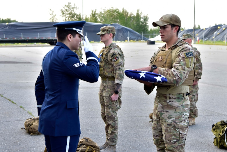 U.S. Air Force Senior Airman Javier Barraza, a 354th Force Support Squadron ceremonial guardsman, salutes a flag held by Staff Sgt. Anthony Vega, the 354th Civil Engineer Squadron Explosive Ordnance Disposal (EOD) flight noncommissioned officer in charge of operations, during a ceremony on Eielson Air Force Base, Alaska, July 31, 2020. Every year, EOD Airmen ruck 220 miles from Eielson AFB to the Arctic Circle to honor members of the EOD community who paid the ultimate sacrifice. (U.S. Air Force photo by Senior Airman Beaux Hebert)