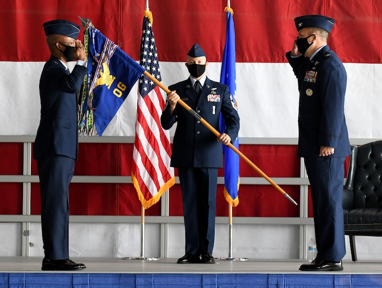 Two Airmen salute each other while a third looks on holding a guideon