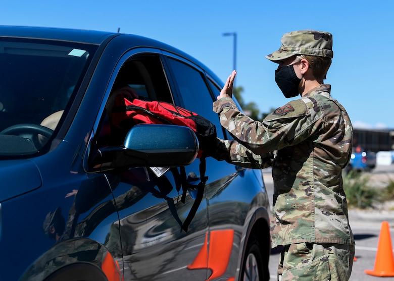 An Airman hands out school supplies.