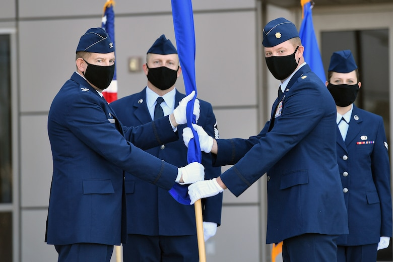 Col. James Smith, Peterson-Schriever Garrison commander, left, and Maj. Justin Gabbard, 21st Comptroller Squadron commander, left, present the furled guidon representing the deactivation of the 50th Comptroller Squadron, July 30, 2020, at Schriever Air Force Base, Colorado. The former squadron was absorbed into a larger 21st CPTS at the Peterson-Schriever Garrison. (U.S. Air Force photo by Dennis Rogers)