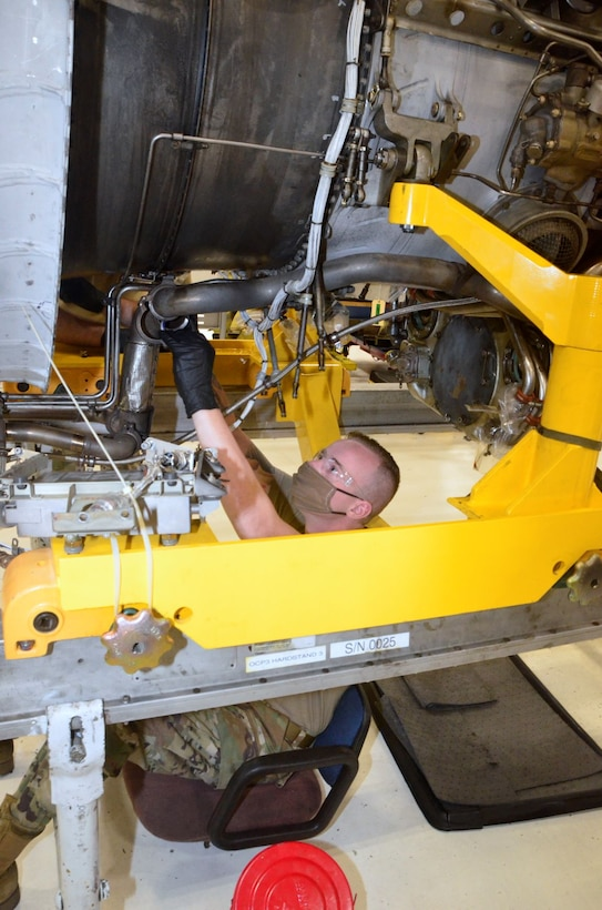 Photo of maintenance personnel installing an engine part
