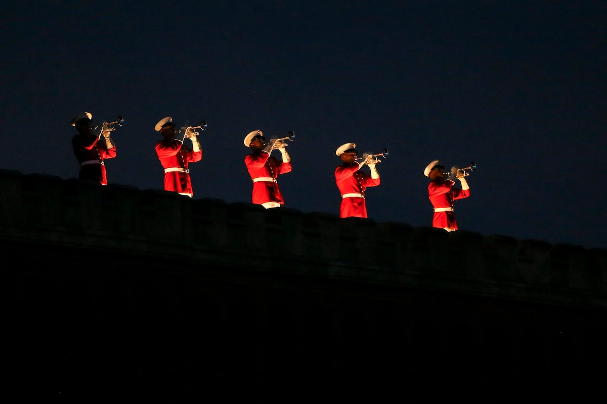 Five Marine Corps buglers perform in a line atop a building at night.