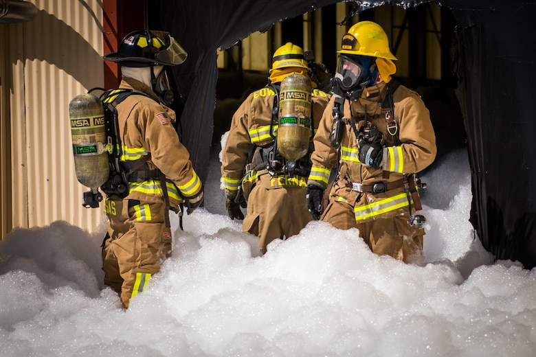 Firefighters from the Edwards Air Force Base Fire and Emergency Services conduct search and rescue training at a recently remodeled hangar at Edwards Air Force Base, California, July 23. Firefighters were tasked with locating a simulated victim amidst the fire suppressant foam deployed throughout the hangar. (Air Force photo by Chris Dyer)
