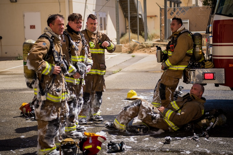 Firefighters from the Edwards Air Force Base Fire and Emergency Services take a break following search and rescue training at a recently remodeled hangar at Edwards Air Force Base, California, July 23. Firefighters were tasked with locating a simulated victim amidst the fire suppressant foam deployed throughout the hangar. (Air Force photo by Chris Dyer)