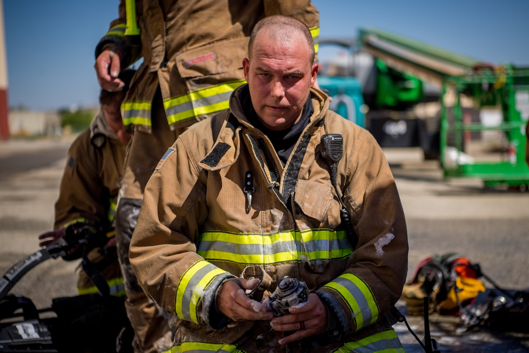 Firefighter John Templeton takes a break following search and rescue training at a recently remodeled hangar at Edwards Air Force Base, California, July 23. Firefighters were tasked locating a simulated victim amidst the fire suppressant foam deployed throughout the hangar. (Air Force photo by Chris Dyer)