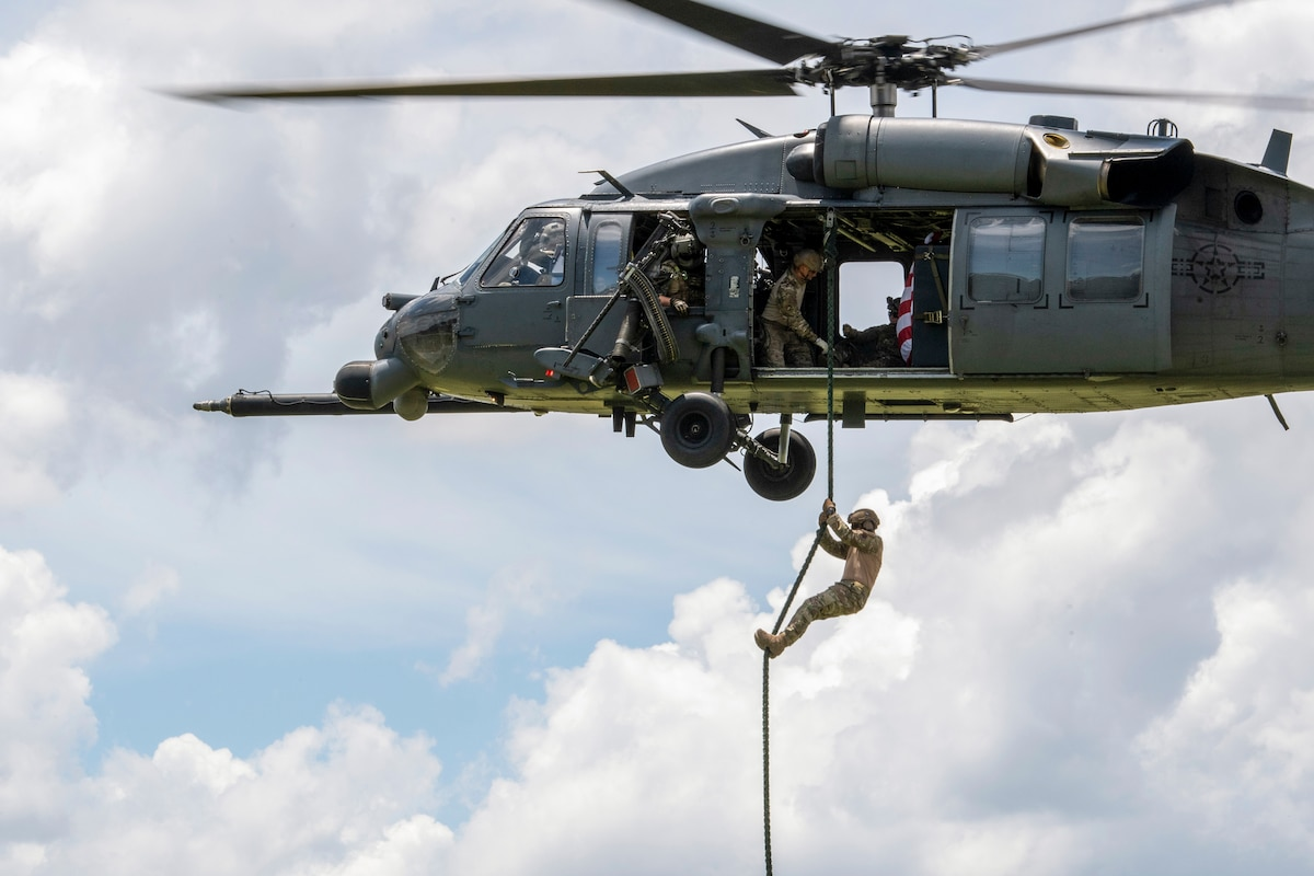 An airman fast-ropes out of a helicopter where others watch.