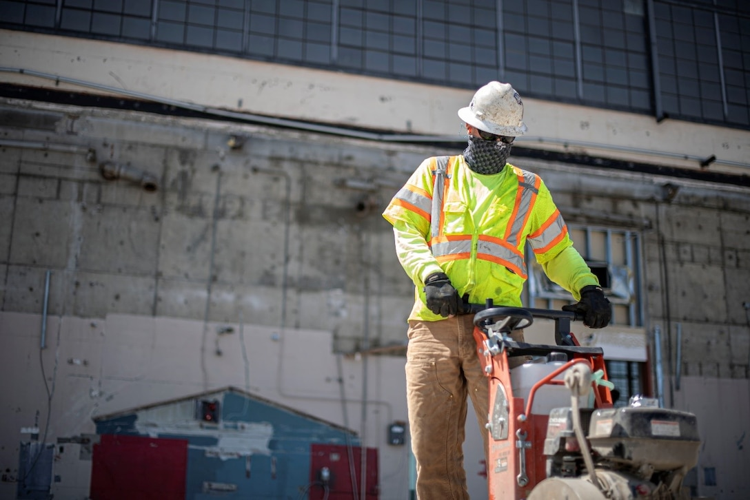 A construction worker uses a jackhammer on a length of pavement off-screen. He is hard at work and wearing bright clothing