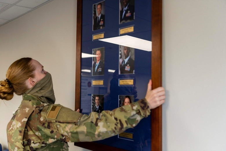 Airman 1st Class Alexandria, force management technician with the 432nd Support Squadron, carefully places a command board on the wall of the newly renovated consolidated support center at Creech Air Force Base.