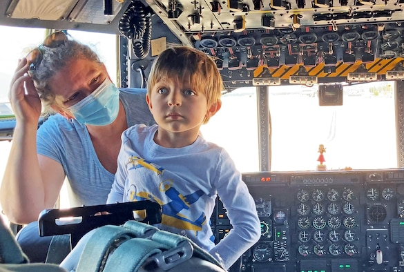 Young boy and mother stand inside cockpit of large plane.