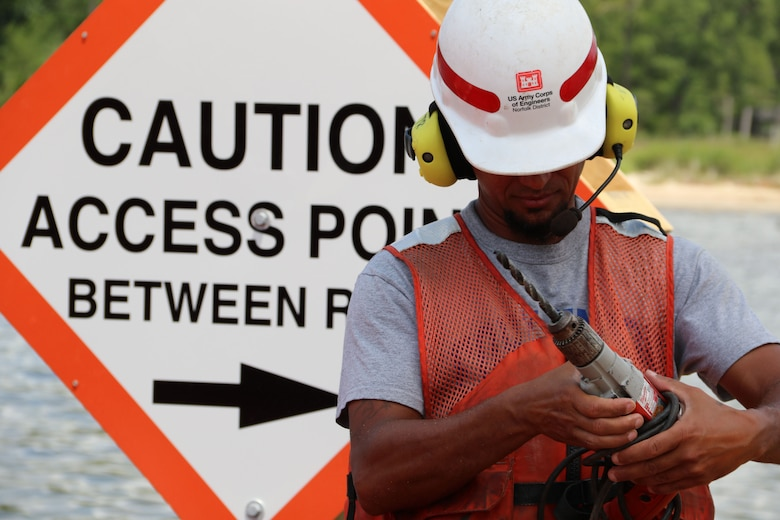 """Man in front of sign that reads, """"CAUTION Access Point Between Reefs"""" and holds drill"""