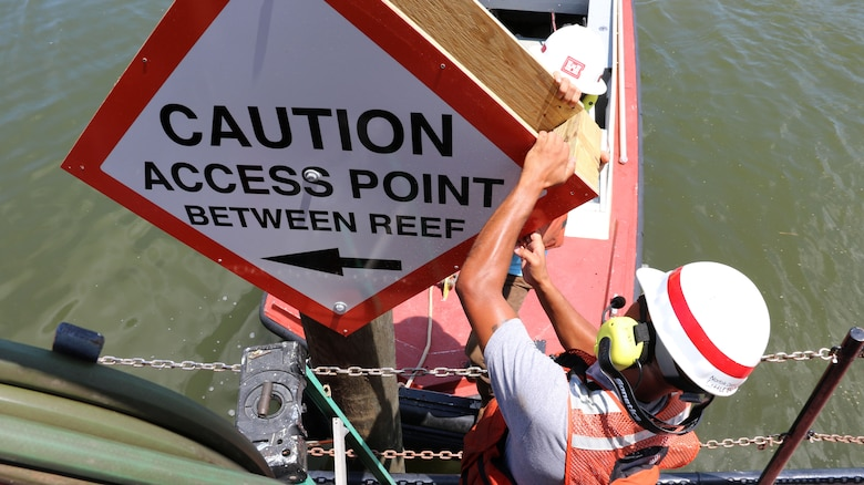 """man in life jacket holds sign on a pole in the water that reads, """"CAUTION Access Point Between Reefs"""""""