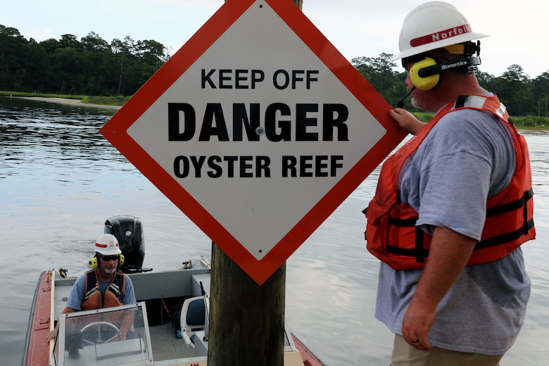 """two men in life jackets, one in a small boat, are in the frame with a sign that says, """"Keep Off Danger Oyster Reef"""""""