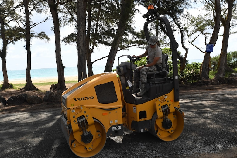 A photo of U.S. Air Force Senior Airman Pleiades Dolor, 624th Civil Engineer Squadron heavy equipment specialist, leveling the ground in preparation for pavement repairs at Bellows Air Force Station, Hawaii, July 22, 2020, during the unit's Annual Training. The U.S. Air Force Reserve's 624th CES provided necessary repairs at Bellows AFS, a Military Welfare and Recreation facility that supports military families and communities, to improve infrastructure and increase individual readiness skills. (U.S. Air Force photo by Tech. Sgt. Garrett Cole)
