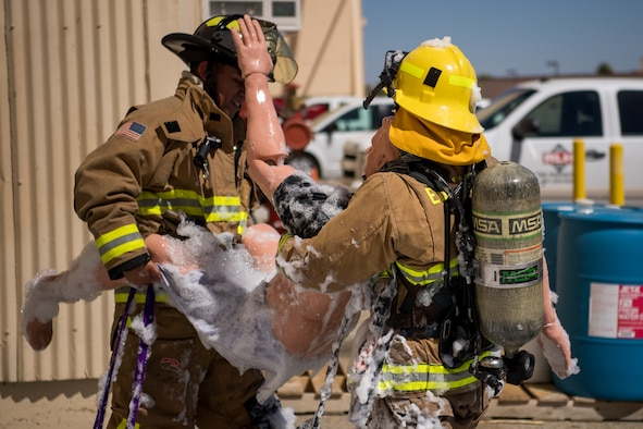 Firefighters Senior Airman Rene Rosas and Brody Deal evacuate a simulated victim during search and rescue training at a recently remodeled hangar at Edwards Air Force Base, California, July 23. The unique training opportunity provided the firefighters a mentally and physically demanding training scenario. (Air Force photo by Chris Dyer)