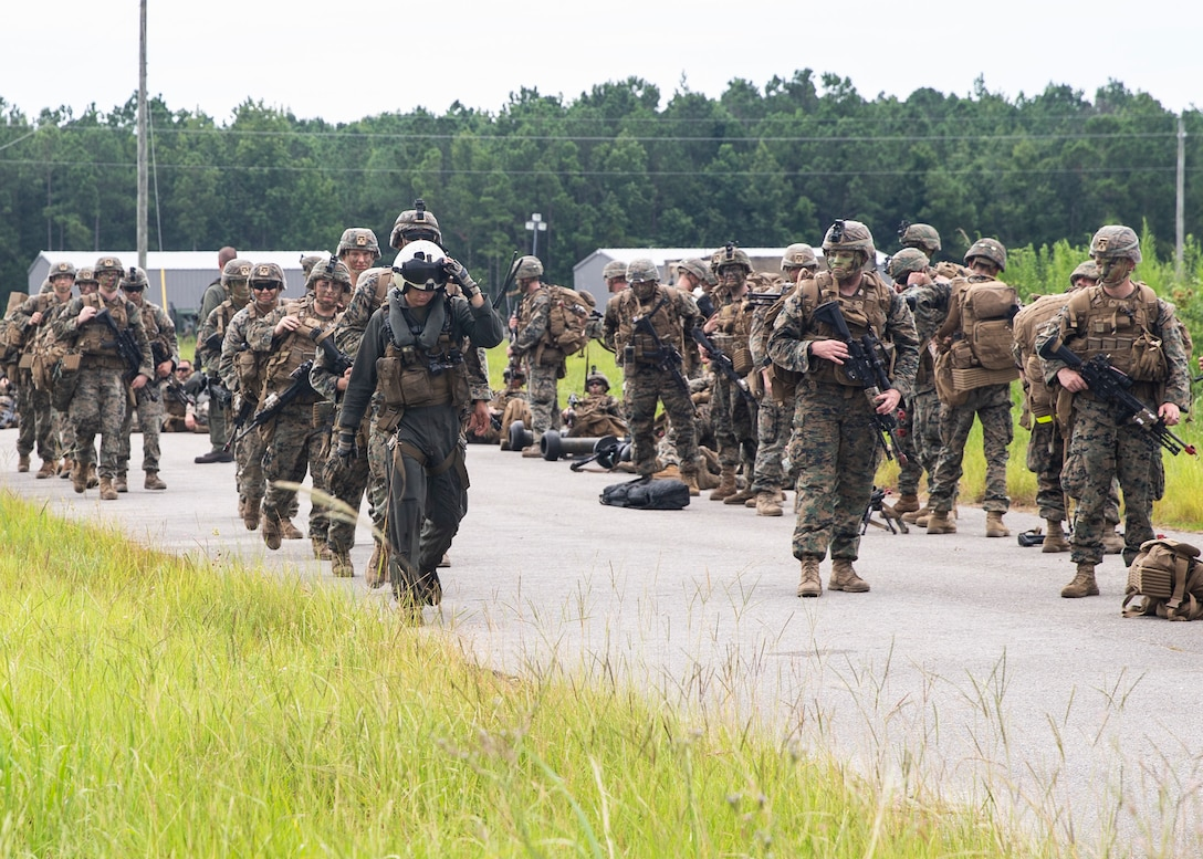 A crew chief with Marine Heavy Helicopter Squadron 366, 2nd Marine Aircraft Wing, leads Marines with 3rd Battalion, 6th Marine Regiment to board a CH-53E Super Stallion during Exercise Deep Water 2020 at Marine Corps Air Station New River, N.C., July 29, 2020. The purpose of the exercise is to increase 2nd Marine Aircraft Wing's interoperability and readiness on a scale that simulates peer-level threats. (U.S. Marine Corps photo by Lance Cpl. Yuritzy Gomez)