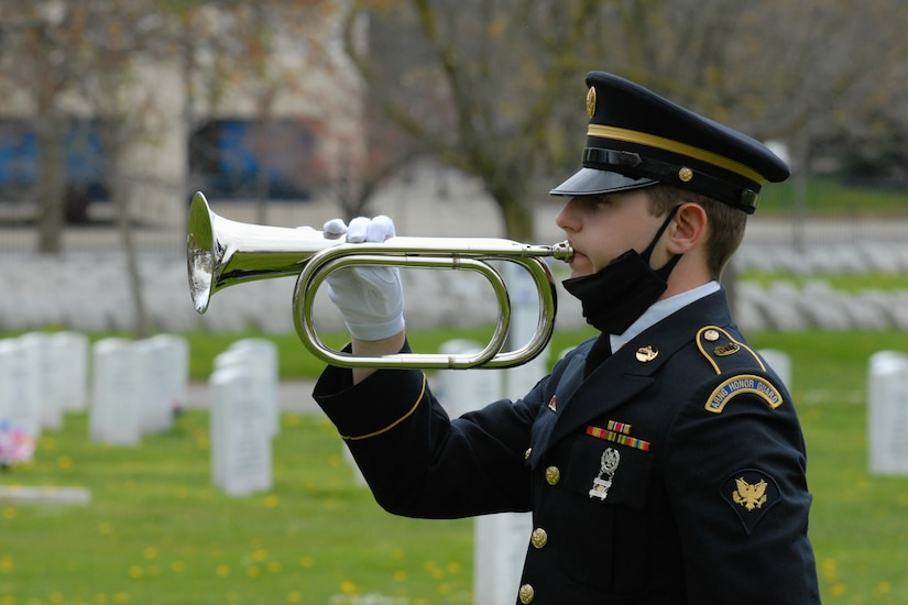 Honor guard soldier plays a trumpet at a military funeral.