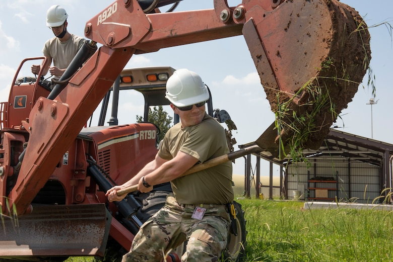 Photo of an Airman using a shovel to dislodge dirt from a trench machine