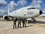 Three navy pilots stand in front of an airplane