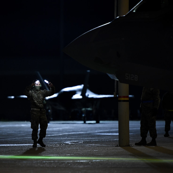 A photo of an Airman marshaling and F-35