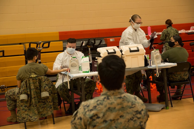 U.S. Marines wait their turn to donate blood during an Armed Services Blood Program (ASBP) blood drive at Hopkins Gymnasium on Camp Elmore, Norfolk, Virginia, May 28, 2020.