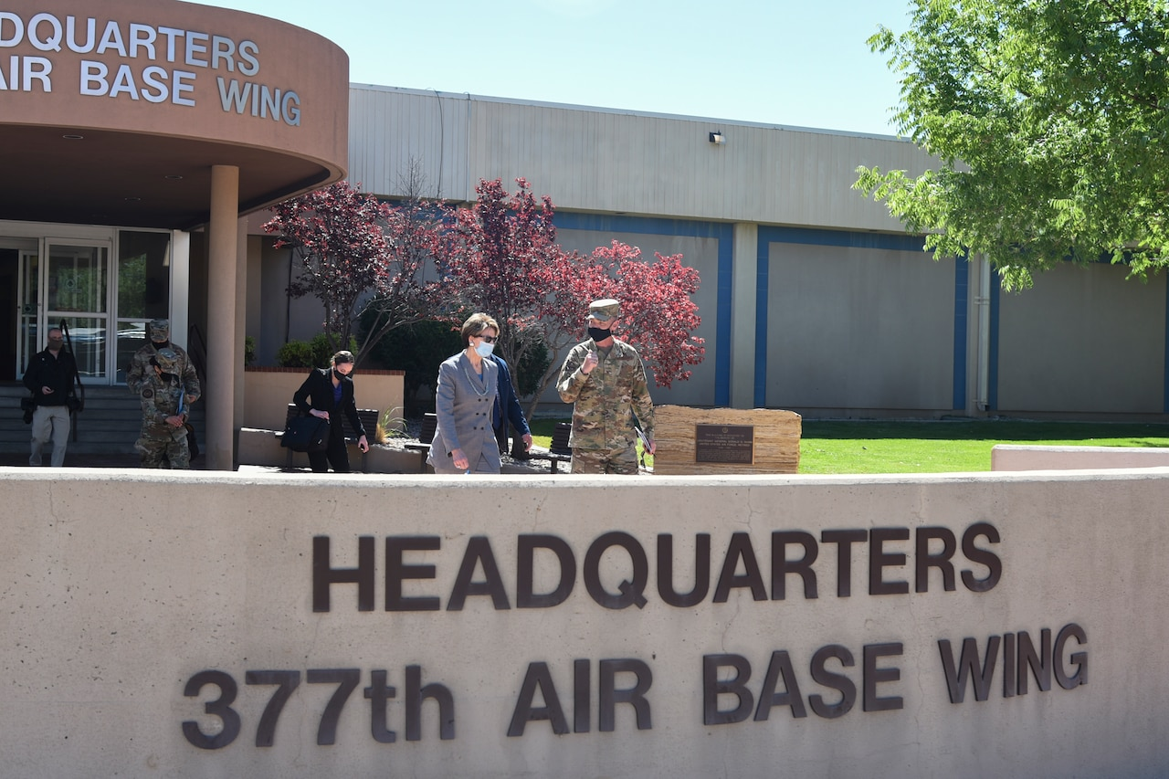 A woman and an airman, both wearing masks, talk while walking out of a headquarters building..