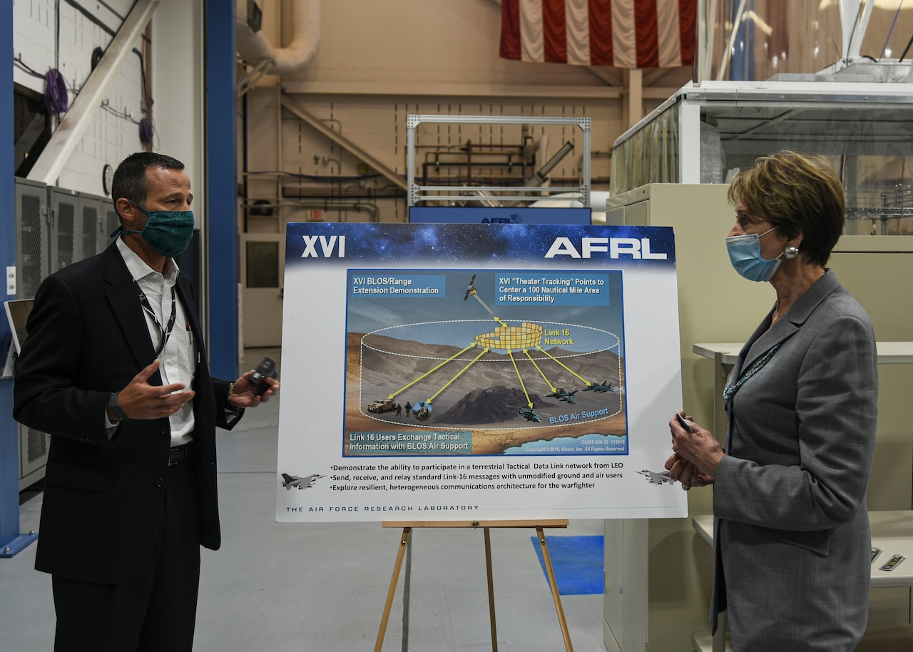 A man and a woman speak while standing by a sign depicting part of a military unit's operations. Both are wearing masks.