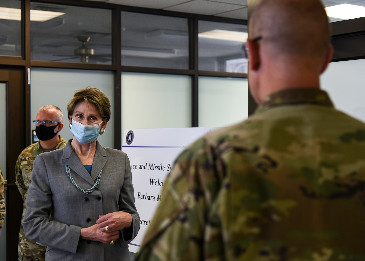 A woman wearing a mask receives a briefing from an airman who has his back to the camera.