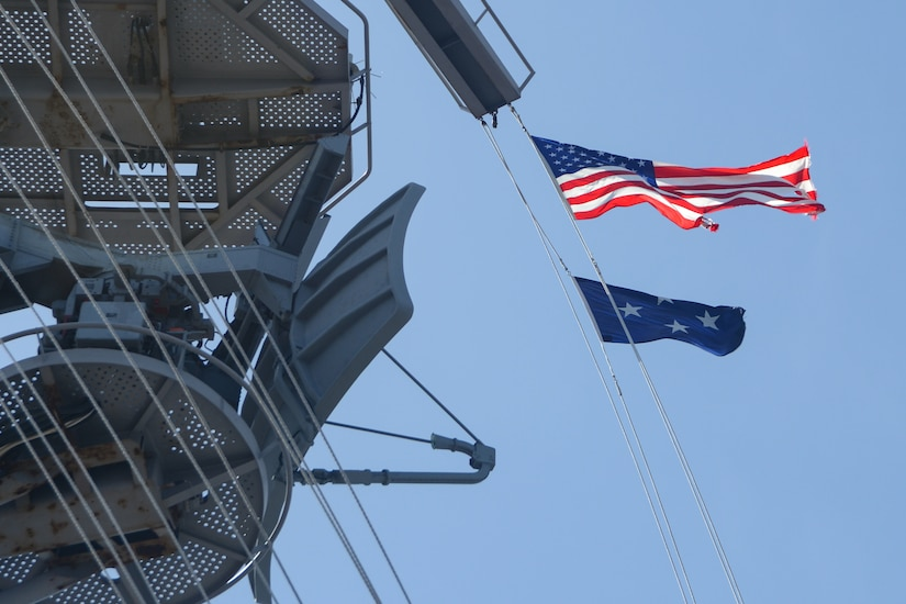 An American flag and a four star flag blow in the wind on a ship.