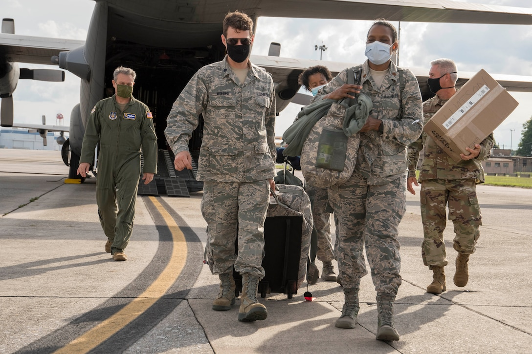 Nurses from the 94th Aeromedical Staging Squadron and members of the greeting party, including Col. Craig McPike, 94th Airlift Wing commander, left, depart a C-130H3 Hercules on the flightline at Dobbins Air Reserve Base, Ga. May 28, 2020. Four nurses from Dobbins mobilized to the COVID-19 frontlines in New York City as part of the whole-of-government response to the pandemic. (U.S. Air Force photo/Andrew Park)