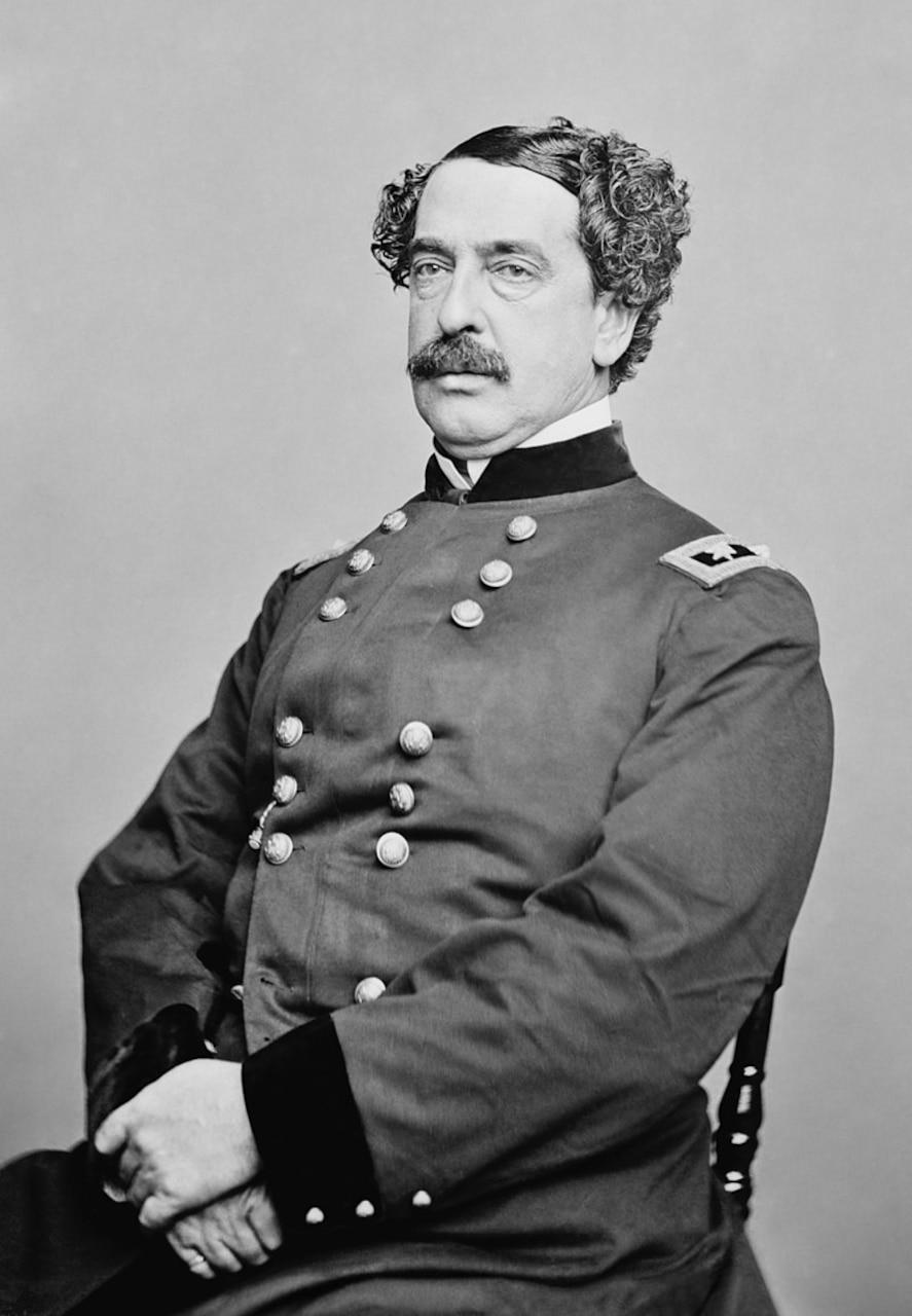 A man in a Civil War-era uniform poses for a portrait.