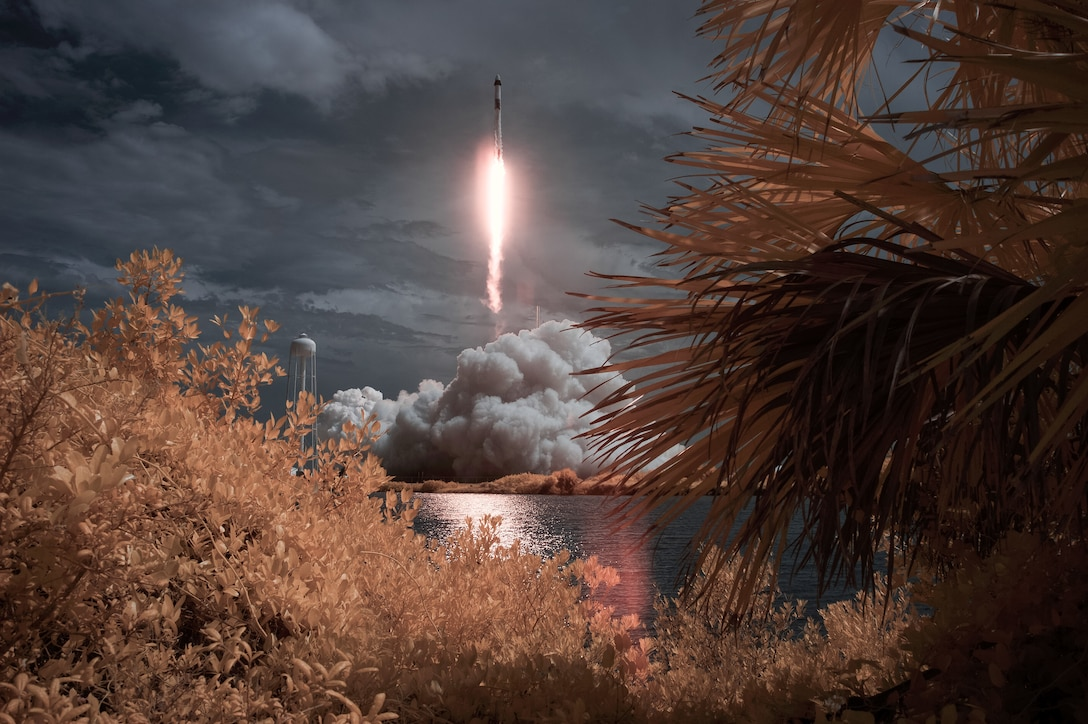 A flash of light and clouds of smoke are seen in the distance, framed by foliage, as a rocket takes off.