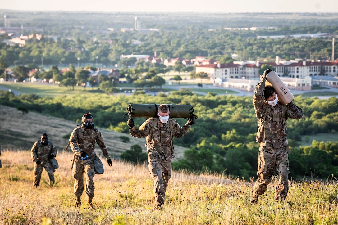 Soldiers walk up a hill carrying different items.