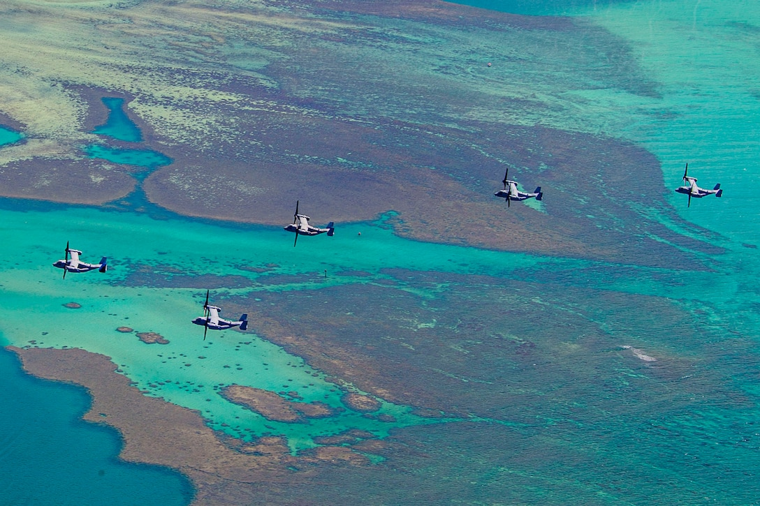 Five Marine Corps aircraft fly over an island.