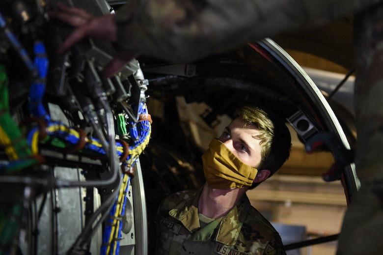 Airman 1st Class Jerrert Green receives training from Staff Sgt. Jonathan Daniels, both 62nd Maintenance Squadron jet mechanics, on the engine of a C-17 Globemaster III on Joint Base Lewis-McChord (JBLM), Wash., May 20, 2020. Airmen have still arrived to their first duty stations during the COVID-19 pandemic and units at JBLM have made it a priority to make sure they are integrated into their new units and start receiving training. (U.S. Air Force photo by Airman 1st Class Mikayla Heineck)