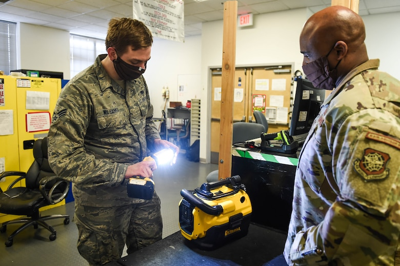 Senior Airman Michael Wilbanks, 62nd Maintenance Squadron support section journeyman, left, tests a flashlight before checking it out to Senior Master Sgt. John Williams, 62nd Mainenance Squadron flight chief, right, inside the home station check support section on Joint Base Lewis-McChord, Wash., May 20, 2020. The support section provides tools and equipment to maintenance personel who work on the aircrafts. (U.S. Air Force photo by Airman 1st Class Mikayla Heineck)