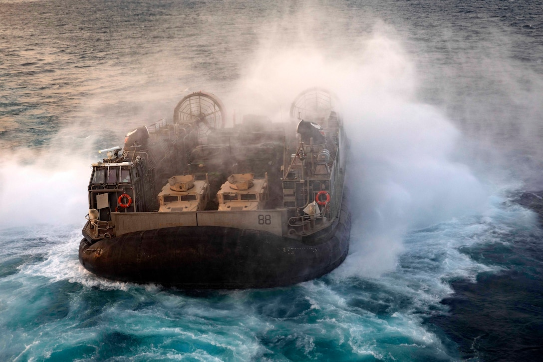 An air-cushioned landing craft travels through waters.