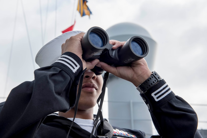 A sailor looks through a pair of binoculars.