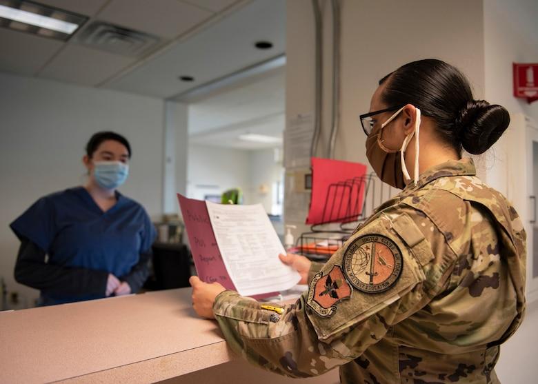 Tech. Sgt. Sara Moreno review a patient's form
