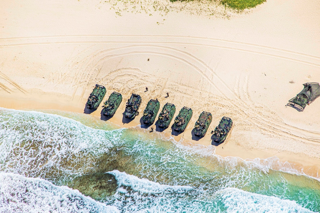 A row of eight vehicles on a beach are seen from above.