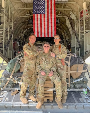 Air Force Reserve Master Sgt. Scott Klobucher (left) and Staff Sgt. Christopher James (right) poses with Chief Master Sgt. Donald Tarrance on the back of a C-130J Hercules loaded with cargo while deployed to Syria in 2019. Tarrance has served for over 40 years in a variety of positions and statuses. (Courtesy photo)