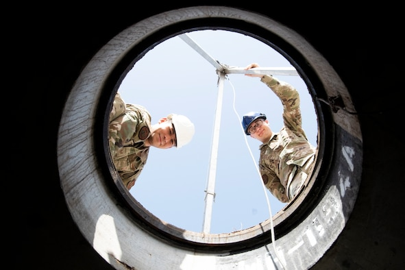 """U.S. Air Force Staff Sgt. Alan Hooper, 39th Communications Squadron cable maintenance supervisor, (left), and Senior Airman Jacob Glass, 39th CS cable and antenna systems technician, stare down a manhole May 20, 2020, at Incirlik Air Base, Turkey.  Cable and antenna systems Airmen, popularly called """"cable dawgs,"""" maintain and install cables on telecommunications towers and underground vaults or maintenance holes. (U.S. Air Force photo by Staff Sgt. Joshua Magbanua)"""
