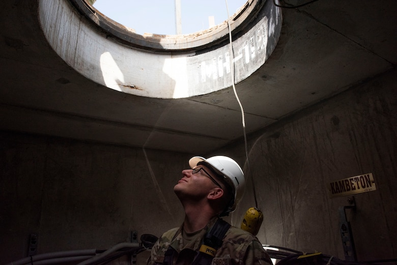 "U.S. Air Force Senior Airman Brandon Gayton, 39th Communications Squadron cable and antenna systems technician, looks up through a manhole May 20, 2020, at Incirlik Air Base, Turkey. Cable and antenna systems Airmen, commonly called ""cable dawgs,"" check oxygen levels before entering an underground chamber as a safety precaution. (U.S. Air Force photo by Staff Sgt. Joshua Magbanua)"