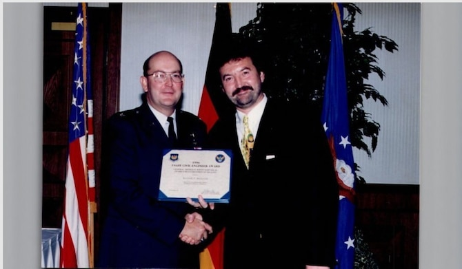 Mr. Rainer Mueller (right), 86th Civil Engineer Squadron installation management flight chief poses for a photo with retired Brig. Gen. Charles Fox after receiving the United States Air Forces in Europe Civil Engineer Award at Ramstein Air Base, Germany, 1996. Within 86th CES, Mueller put all of his attention into mitigating the base's environmental impact; and did so with great success. (Courtesy photo by Herr Rainer Mueller)