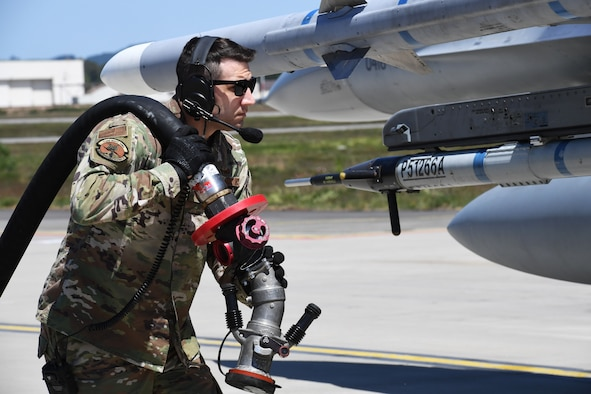 "U.S. Air Force Master Sgt. Jayson Lyons, 435th Contigency Response Group readiness and training flight chief, brings a fuel hose to an F-16 Fighting Falcon during Exercise Agile Wolf at Ramstein Air Base, Germany, May 28, 2020. The exercise tested the ability to perform a ""hot-pit refuel"" during a contingency operation. (U.S. Air Force photo by Airman 1st Class Alison Stewart)"