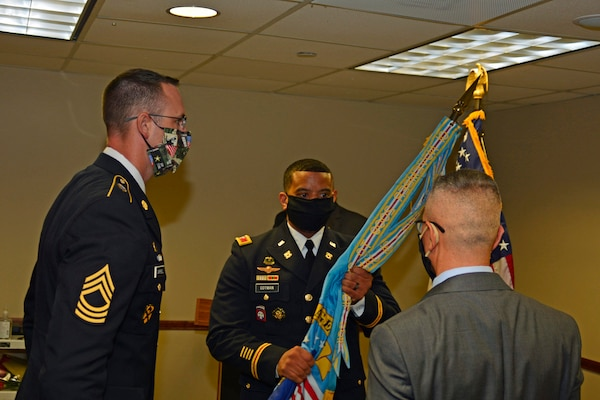two Army members and a senior civilian member pass a flag in a cermony