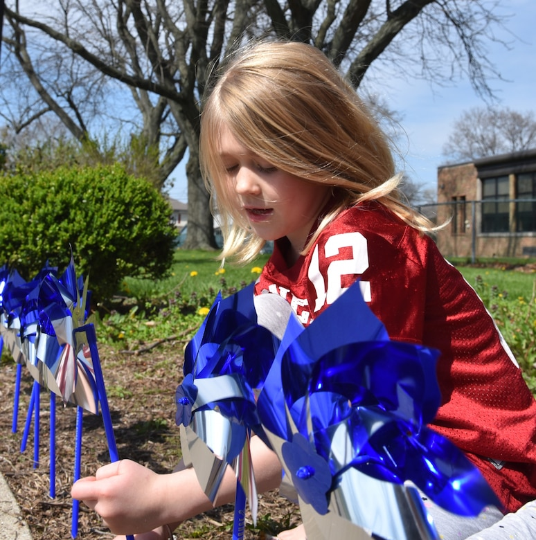 Child places blue pinwheel in ground.